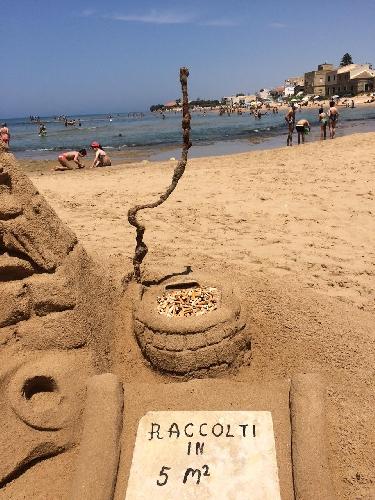https://www.ragusanews.com//immagini_articoli/29-06-2017/scultura-sabbia-raccoglie-cicche-sigarette-500.jpg